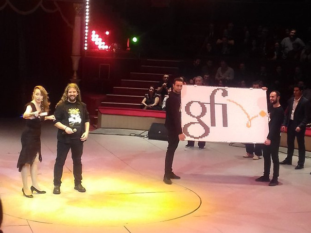 Eduardo Tavares and his huge origami pixels mosaic with the Gfi logo, at the Gfi Got Talent 2018 event at the Cirque d'Hiver in Paris.<br/>
